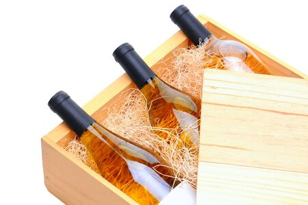 Closeup of three white wine bottles on their side in a wooden crate. Crate lid is pulled partially back exposing the bottles and packing excelsior. Horizontal format isolated on white. Stock Photo - 9961106