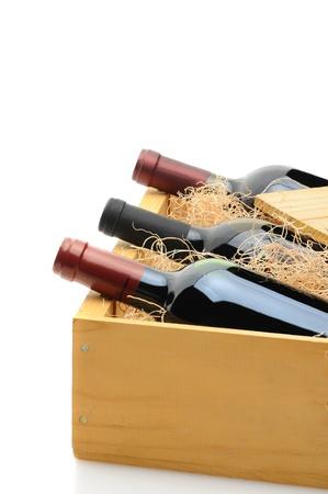 Close-up van drie flessen rode wijn in een houten verzending krat. De kist is gedeeltelijk open met excelsior verpakking. Verticale indeling op een witte achtergrond met reflectie.