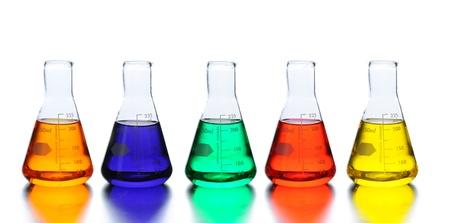 Vijf laboratorium bekers met vloeistof van diverse kleuren. Close-up in horizontale formaat met reflecties.