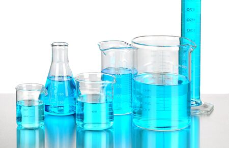 Assorted laboratory beakers and scientific glassware filled with a blue liquid chemical. Closeup in horizontal format with reflections.