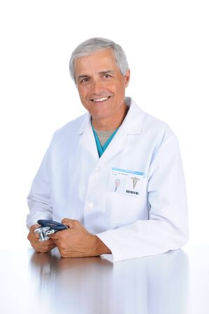 50 yrs: Smiling middle aged doctor seated and holding his stethoscope in both hands. Man is wearing a lab coat and scrubs in vertical format over a white background.
