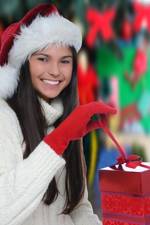 happy christmas: Attractive smiling young woman opening a Christmas Present. Vertical format with out of focus background.