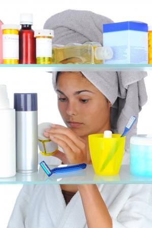 medicamentos: Joven mirando la botella de prescripci�n en frente de un gabinete de medicina del ba�o. Formato vertical aislada sobre fondo blanco.