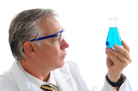 Profile shot of a middle aged scientist examining a blue liquid in a beaker isolated over white. Horizontal format.