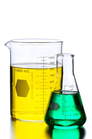 Closeup of Glass Two Beakers with Green and Yellow Liquids on a lab table with reflections. Vertical format isolated on white. Stok Fotoğraf