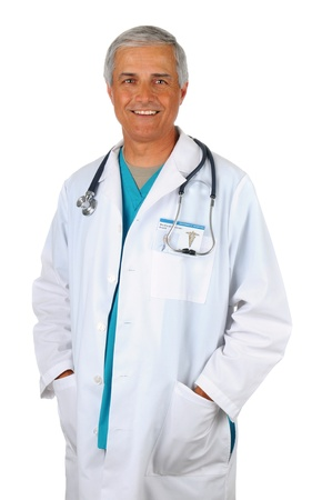 surgical scrubs: Smiling Middle Aged Doctor Standing with his hands in the pockets of a Lab Coat. Man is wearing green surgical scrubs with a stethoscope around his neck. Vertical isolated on white. Stock Photo