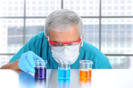 Scientist in modern laboratory with protective mask and goggles examining laboratory beakers filled with diferent chemicals. Horizontal format. Stock Photo - 10100906