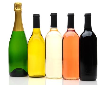 Een groep van vijf wijn en champagne flessen op een witte achtergrond. Flessen hebben geen etiketten en reflectie op voorgrond. Stockfoto