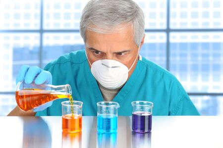 Scientist in modern laboratory pouring and measuring liquids in assorted beakers. Horizontal format. Stock Photo - 10139658