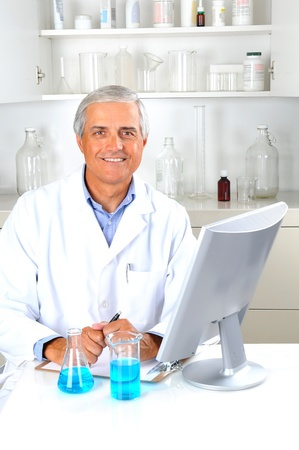 Researcher seated in laboratory setting with beakers of liquid and computer monitor. Vertical format. Stock Photo - 10139680