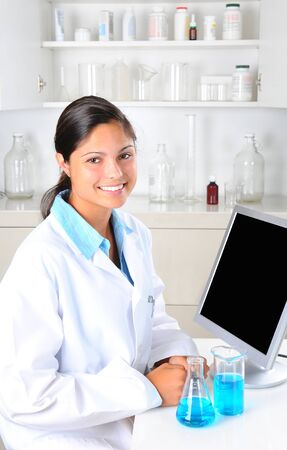 Young female Lab Tech in laboratory setting with beakers of chemicals and computer monitor. Vertical format. Stock Photo - 10139659