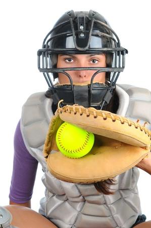 Primer plano de un receptor de softbol femenino que lleva una máscara y protector de pecho la celebración de guante con la pelota en la red frente a ella. Formato vertical aislado en blanco.