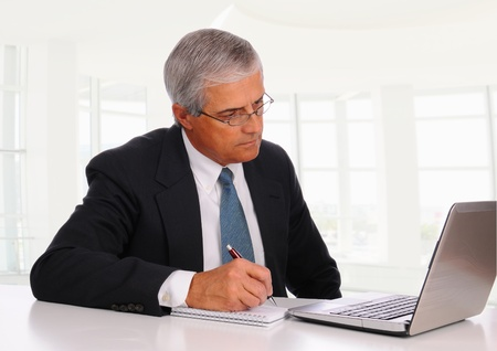 businesspersons: Smiling Middle Aged Businessman at desk using laptop computer with concerned expression. Horizontal format in modern office setting