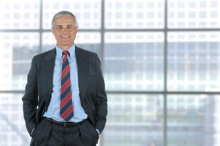 中間の笑みを浮かべてズボンのポケットに手を白で隔離されるビジネスの男性高齢者。垂直形式近代的なオフィスビルの大きな窓の前に立っていま 写真素材