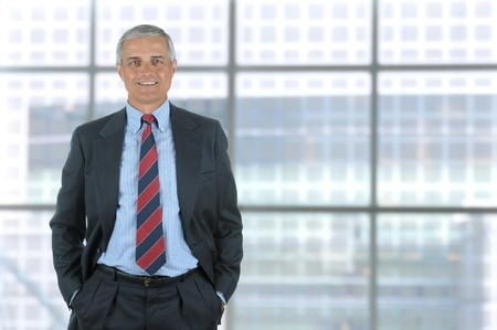 middle aged men: Smiling middle aged business man isolated on white with his hands in pants pockets. Vertical Format standing in front of large window of modern office building.