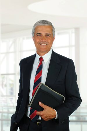 aged: Smiling middle aged businessman in modern office setting holding a small binder. Vertical Format. Stock Photo
