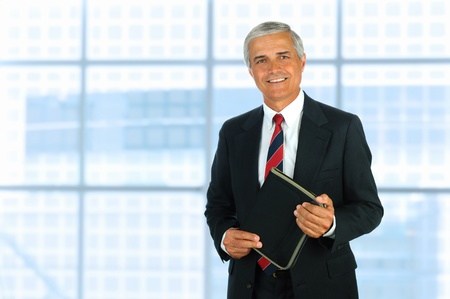 Smiling middle aged businessman in modern office setting holding a small binder. Horizontal Format. photo