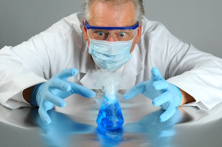 reaction: Closeup of a mad scientist as he observes a chemical reaction in his laboratory. Man is partially hidden behind a glass beaker that is bubbling over and smoking.