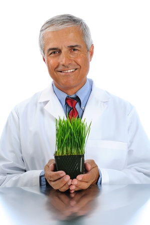 Smiling scientist holding a laboratory grown plant in container in both of his hands. Vertical format isolated over white. Stock Photo