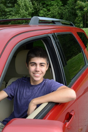 A newly licensed teenage male driver sits in his shiny new red car. Close up in vertical format showing the young caucasian man smiling as he sits behind the wheel. photo