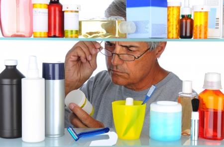 medycyna: Unshaven bliskim wieku człowiek czytania etykietę recepty z przodu jego łazienka gabinet medycyny. Poziome formatu samodzielnie na białym tle.