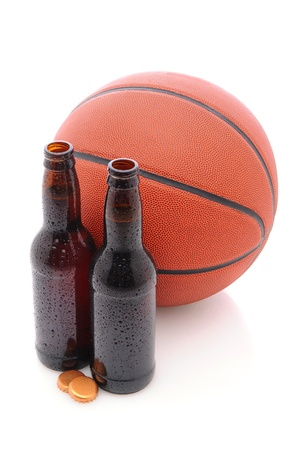 Two Beer Bottles with their caps off in front of a basketball, isolated on white, with slight reflection. Stock Photo - 10562474