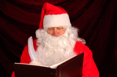 naughty or nice: Closeup of Santa Claus writing in his Naughty and Nice Book. Horizontal format with a maroon background. Stock Photo