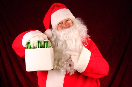 6 pack beer: Santa Claus holding a six pack of beer bottles. Horizontal format with a maroon fabric background