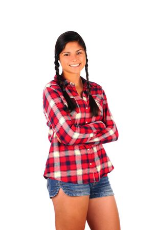 Smiling Teenage Girl in Plaid Shirt and Jean Shorts, standing her arms crossed. Vertical format isolated on white. photo