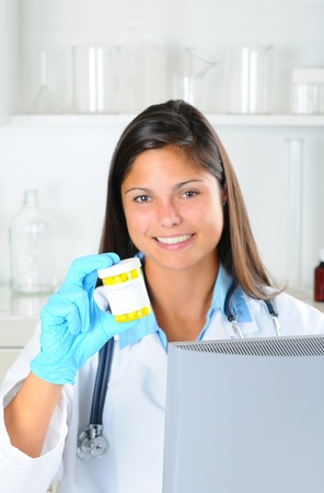 Young female medical professional holding a prescription bottle. Woman is seated behind a computer monitor in pharmacy setting. Vertical format with shallow depth of field - focus on pill bottle photo