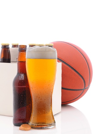 A Basketball Six Pack of Beer Bottles and a Glass of Ale isolated on a white background with reflections in the foreground. photo