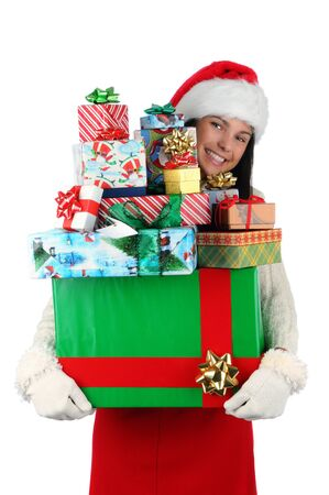 ms: Woman carrying a large stack of christmas presents isolated on white. Woman is peeking around the side of the gifts. Vertical format.