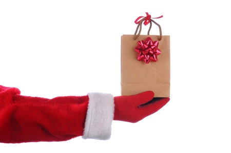 Santa Claus outstretched arm with a gift bag in his hand. Horizontal format over a white background. Stock Photo - 10828543