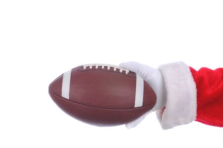 st claus: Santa Claus outstretched arm with an american football ready to hand off. Horizontal format over a white background. Stock Photo