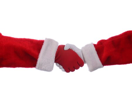 Two Santa Claus shaking hands over a white background. One Hand is in a red glove the other is wearing a white glove. Фото со стока