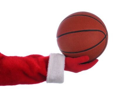 Santa Claus outstretched arm holding a Basketball. Horizontal format over a white background. photo
