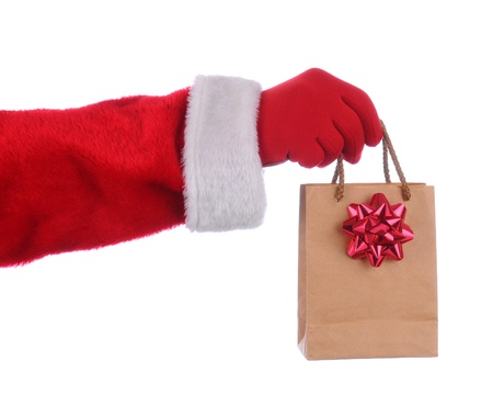 Santa Claus outstretched arm holding a gift bag by its handles. Horizontal format over a white background. Stock Photo - 10876966