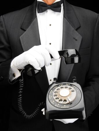 Closeup of a man in a tuxedo holding retro rotary dial telephone in his hands with the receiver in one hand held partially up.