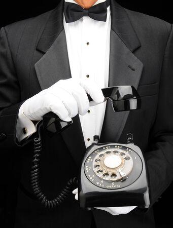 hand held: Primo piano di un uomo in smoking tenendo retr� telefono a linea nelle sue mani con il ricevitore in una mano tiene parzialmente in su.