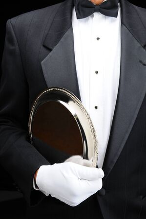 serving tray: Closeup of af butler with a silver tray under his arm. Man is wearing a tuxedo and white gloves showing torso only in vertical format. Stock Photo