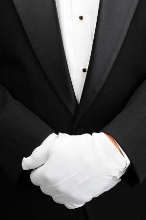 tuxedo man: Closeup di un maggiordomo con le mani in guanti bianchi di fronte al suo corpo. L'uomo indossa uno smoking che mostra solo il suo busto in formato verticale. Archivio Fotografico