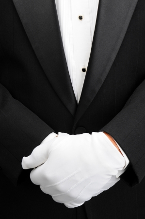 Closeup of a butler with his white gloved hands in front of his body. Man is wearing a tuxedo showing only his torso in vertical format. Foto de archivo