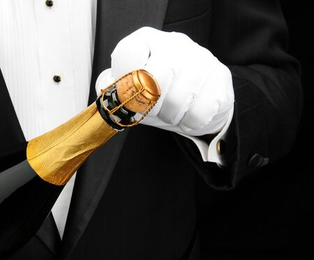Closeup of a waiter opening a bottle of champagne.