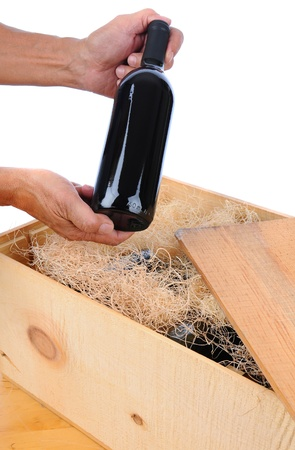 Man holding a single wine bottle over wooden crate filled with bottles and packing material. Vertical isolated over white. photo