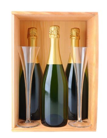 Drie flessen champagne en twee fluiten in een houten kist op een witte achtergrond.