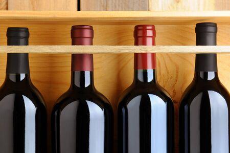 Close-up van vier flessen rode wijn in een houten kist.