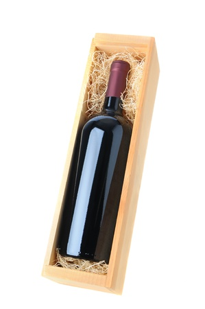 A single red wine bottle in wood box with straw packing over a white background. photo