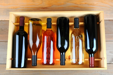 A wooden case of assorted wine bottles without labels on a wood plank winery floor. Horizontal format overhead view. photo
