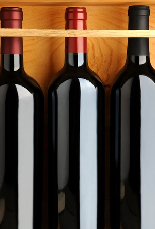 Closeup of three red wine bottles in a wooden case. Vertical format. photo