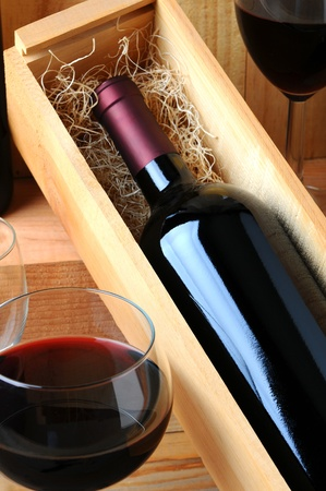 A red wine bottle in a wooden box filled with straw on a tasting room table with two glasses of poured wine.